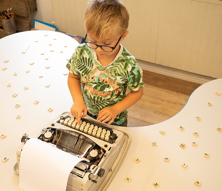 Child using typewriter at daycare